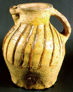 A spouted pitcher with thumbed base used as a decanter at table